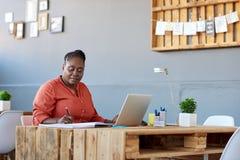 采取笔记和研究膝上型计算机的被聚焦的非洲女实业家 库存照片