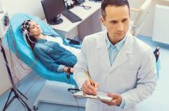 采取笔记的严肃的医生在脑波记录仪做法期间 免版税库存照片