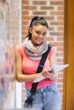 采取笔记的俏丽的微笑的学生在布告牌旁边 库存图片