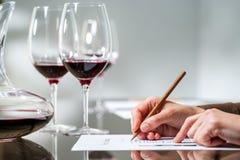 采取笔记的女性手在红葡萄酒品尝 库存照片