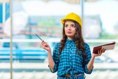采取笔记的妇女建造者在建造场所 免版税库存照片