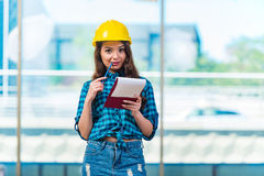 采取笔记的妇女建造者在建造场所 免版税图库摄影