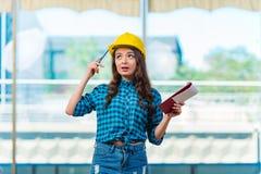 采取笔记的妇女建造者在建造场所 免版税库存图片