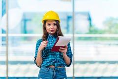 采取笔记的妇女建造者在建造场所 图库摄影