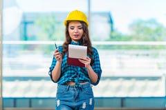 采取笔记的妇女建造者在建造场所 库存图片