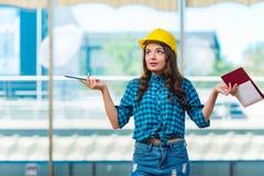采取笔记的妇女建造者在建造场所 库存照片