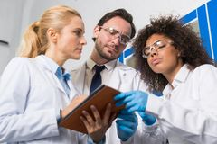 采取笔记的小组科学工作者做研究对实验室,混合写结果的科学家种族队  免版税库存照片