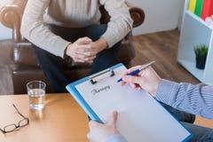 采取笔记的心理学家在精神疗法期间 免版税库存照片