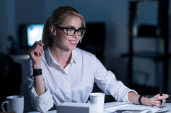 采取笔记的快乐的正面秘书在办公室 库存照片