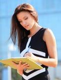 采取笔记的成功的女实业家 免版税库存图片