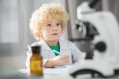 采取笔记的白色实验室外套的男小学生在科学实验期间 库存图片