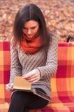 采取笔记的长凳的可爱的妇女 免版税库存图片