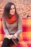 采取笔记的长凳的可爱的妇女 免版税图库摄影