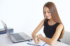 采取笔记的年轻女商人 免版税库存图片