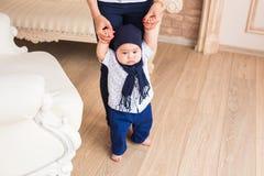 采取第一步在母亲帮助下的婴孩 免版税库存照片