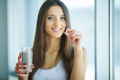 采取维生素药片的美丽的微笑的妇女 饮食补充条款 免版税库存图片