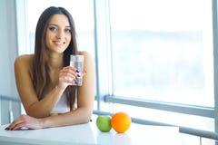 采取维生素药片的美丽的微笑的妇女 饮食补充条款 免版税库存照片