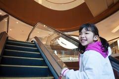 采取自动扶梯的亚洲孩子 免版税图库摄影