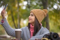 采取自已与智能手机照相机的妇女愉快的女孩图片selfie户外在公园 库存照片