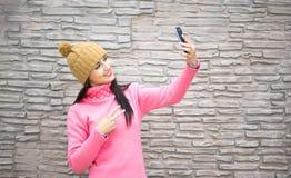 采取自已与智能手机照相机的妇女愉快的女孩图片selfie户外在秋天公园 库存图片