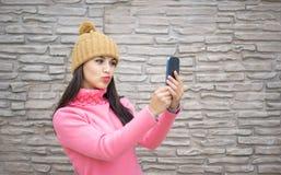 采取自已与智能手机照相机的妇女愉快的女孩图片selfie户外在秋天公园 免版税库存照片
