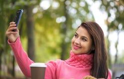 采取自已与智能手机照相机的愉快的女孩图片selfie户外在秋天公园 库存图片