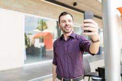 采取自画象的人使用在商城的手机 图库摄影