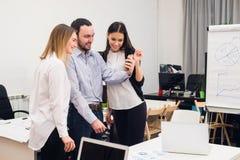 采取自画象和做滑稽的姿态用手的小组四个不同的快乐的工友在小办公室 免版税图库摄影