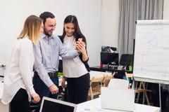 采取自画象和做滑稽的姿态用手的小组四个不同的快乐的工友在小办公室 免版税库存照片