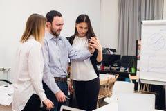 采取自画象和做滑稽的姿态用手的小组四个不同的快乐的工友在小办公室 库存图片