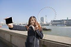 采取自画象的愉快的妇女通过手机反对伦敦眼在伦敦,英国,英国 免版税图库摄影