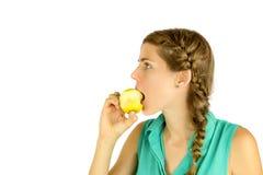 采取苹果的叮咬的女孩。 免版税库存图片