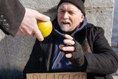 采取苹果的可怜的无家可归的人 免版税库存图片