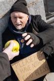 采取苹果的贫穷的年长人 库存照片