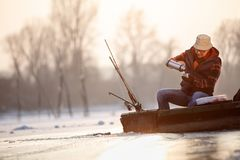 采取茶的小船的人,当钓鱼鱼在冬天时 免版税库存照片