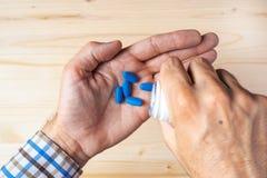 采取蓝色药片的顶视图成人人pov 免版税库存图片