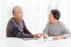 采取血压的资深夫妇在客厅 免版税库存照片