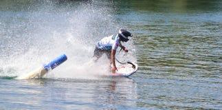 采取角落的男性Motorsurf竞争者以创造很多浪花的速度 图库摄影