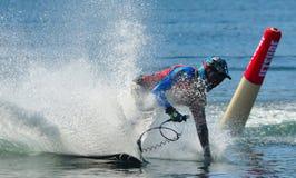采取角落的男性Motosurf竞争者以创造很多浪花的速度 免版税库存图片