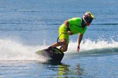 采取角落的男性Motosurf竞争者以创造很多浪花的速度 库存图片