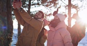 采取记忆的乐趣selfies在与电话的一个冬日他们的激动的小组朋友的感觉愉快和 股票录像