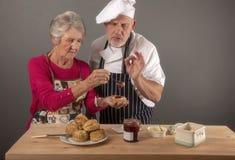 采取资深的妇女烹调与厨师的教训 库存图片