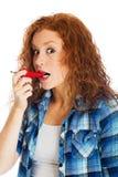 采取辣红辣椒的叮咬红头发人妇女 库存图片