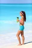 采取连续断裂饮用水的海滩赛跑者 图库摄影