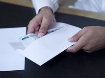 采取金钱的男性手在信封外面 库存图片