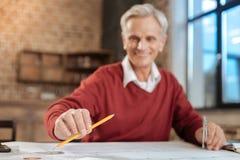 采取铅笔的微笑的工程师,当工作在图纸时 免版税库存照片