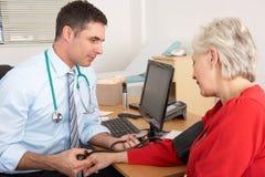 采取高级妇女的血压的英国医生 库存图片