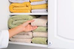 采取从亚麻制壁橱的妇女毛巾 免版税库存照片