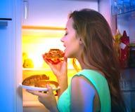 采取从冰箱的十几岁的女孩食物在晚上 库存照片