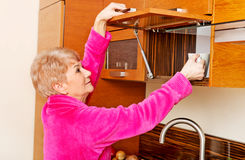 采取从厨柜的微笑资深妇女杯子 免版税库存照片